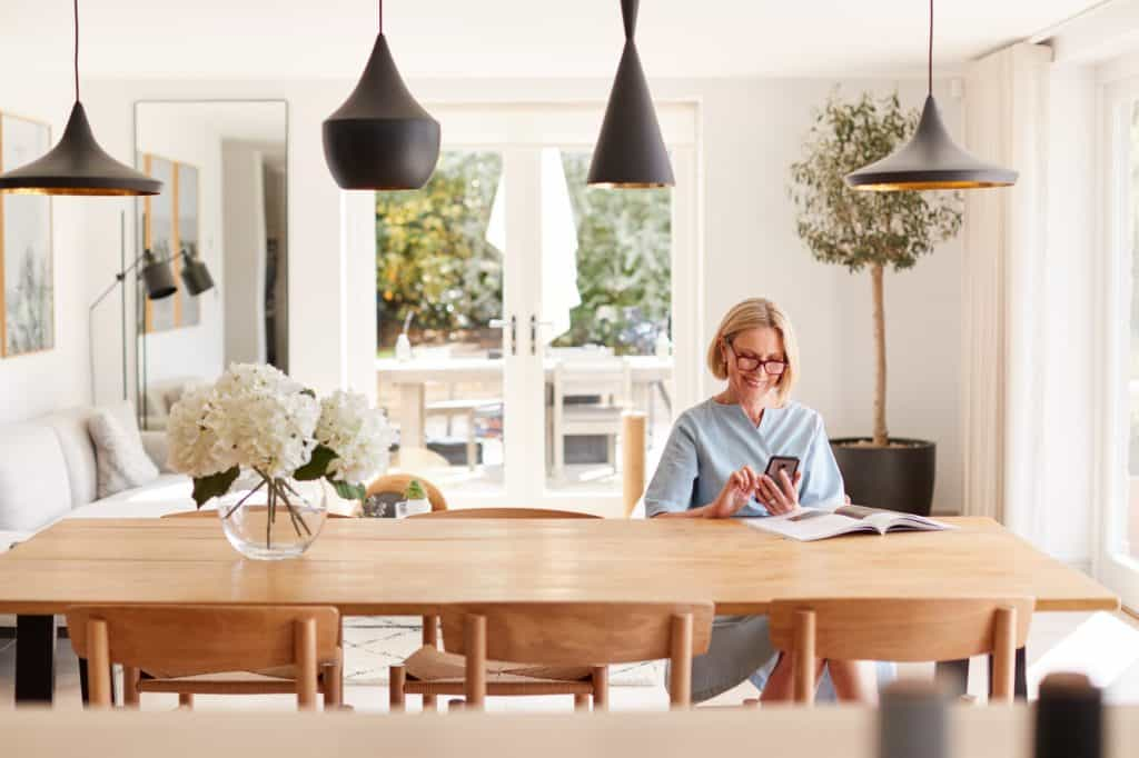 Senior Woman Relaxing With Magazine At Home Looking At Mobile Phone Sitting At Dining Room Table