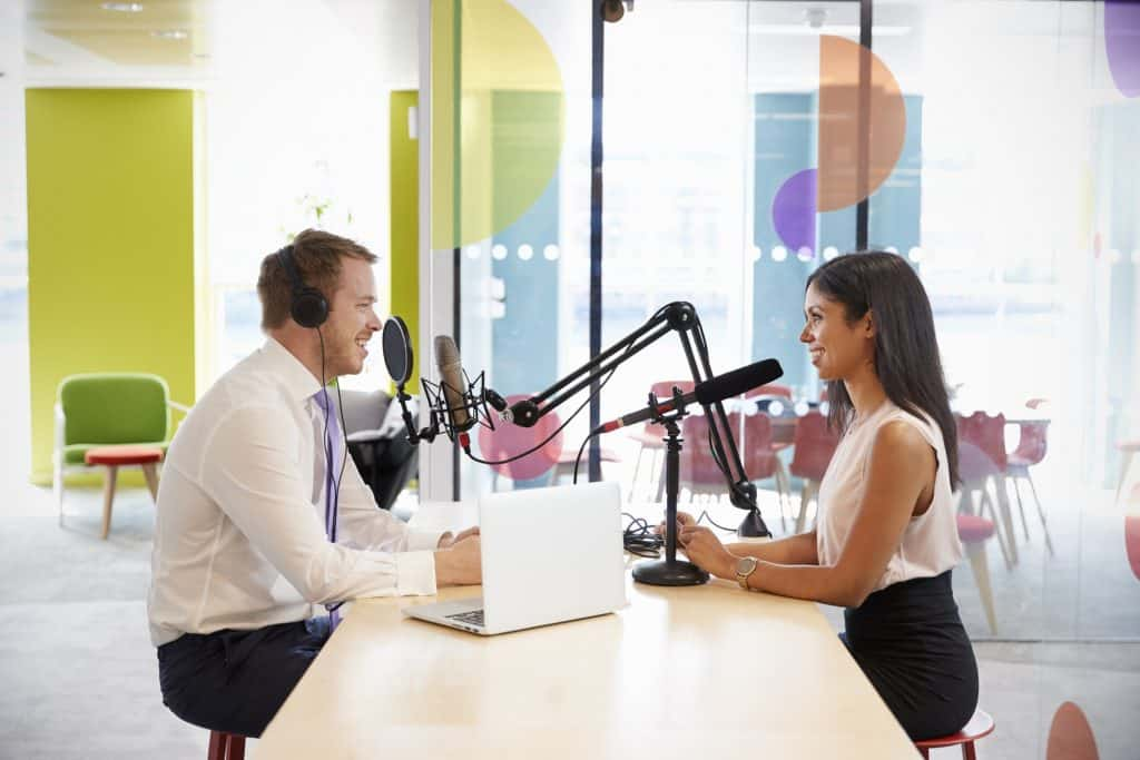Young man interviewing a woman for a podcast